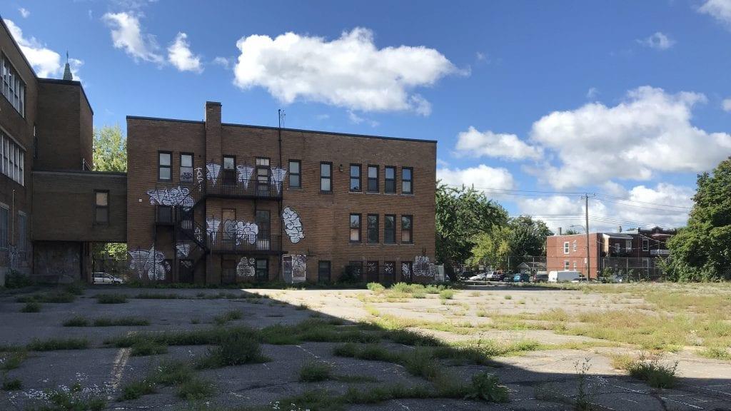 Vue de la cour de l'ex-École Allion avec l'immeuble dans le fond en partie recouvert de graffitis.