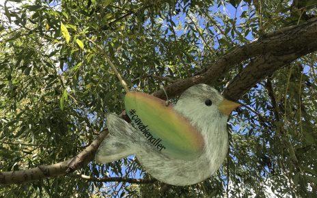 Un oiseau de bois dont les ailes sont aux couleurs de l'arc-en-ciel