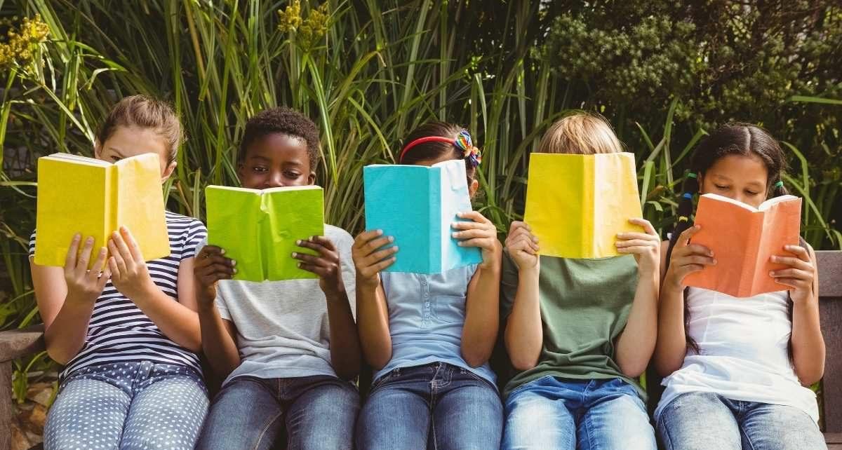 Des enfants en train de lire dans un parc